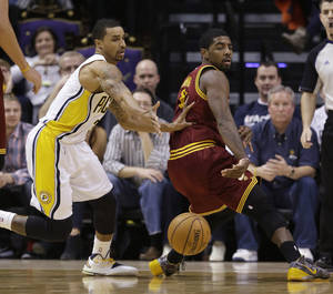 Photo - Cleveland Cavaliers' Kyrie Irving, right,  makes a pass while being defended by Indiana Pacers' George Hill (3) during the second half of an NBA basketball game Tuesday, Dec. 31, 2013, in Indianapolis. Indiana defeated Cleveland 91-76. (AP Photo/Darron Cummings)