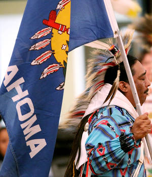 Photo - David Johnson, a member of the Seminole Nation Color Guard, helps lead the Grand Entry at the 38th Annual Spring Powwow at the University of Central Oklahoma's Nigh University Center in Edmond. PHOTOS FROM The Oklahoman Archives <strong>John Clanton -   </strong>