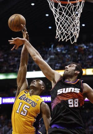 Photo - Los Angeles Lakers' Metta World Peace (15) gets fouled as he goes up for a shot against Phoenix Suns' Hamed Haddadi (98), of Iran, in the first half of an NBA basketball game, Monday, March 18, 2013, in Phoenix. (AP Photo/Ross D. Franklin)