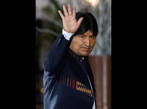 "Photo -   FILE - In this Tuesday, Oct. 2, 2012, Bolivia's President Evo Morales waves to photographers upon his arrival to the Summit of South American and Arab Countries in Lima, Peru. Morales said Friday, Oct. 12, 2012, during a ceremony marking ""Decolonization Day"" that relations with the U.S. Embassy in La Paz have become so bad they are ""like a turd."" (AP Photo/Karel Navarro, File)"