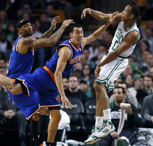 Photo - Boston Celtics' Avery Bradley (0) follows through on a pass past New York Knicks' Pablo Prigioni (9) and Kenyon Martin (3) in the first quarter of an NBA basketball game in Boston, Friday, Dec. 13, 2013. (AP Photo/Michael Dwyer)