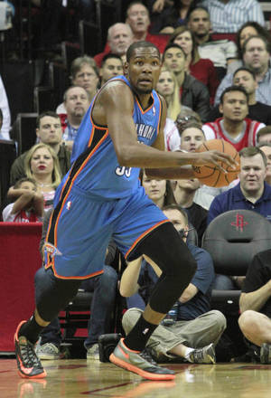 Photo - Oklahoma City Thunder forward Kevin Durant looks up court after grabbing a rebound against the Houston Rockets during an NBA basketball game in Houston Friday, April 4, 2014.   (AP Photo/Richard Carson)