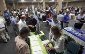 Photo - FILE - In this Monday, July 15, 2013, file photo, people fill up a job fair on Monday, July 15, 2013 in South Burlington, Vt. Small businesses hired at a slow pace during 2013. (AP Photo/Toby Talbot, File)