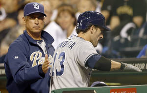 Photo - San Diego Padres manager Bud Black, left, greets Chris Denorfia after he scored the go-ahead run in the ninth inning of a baseball game against the Pittsburgh Pirates on Wednesday, Sept. 18, 2013, in Pittsburgh. The Padres won 3-2. (AP Photo/Keith Srakocic)