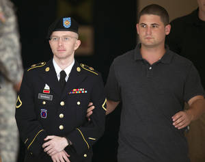 Photo - Army Pfc. Bradley Manning is escorted out of a courthouse at Fort Mead, Md, Thursday, July 25, 2013. Manning is charged with indirectly aiding the enemy by sending troves of classified material to WikiLeaks. He faces up to life in prison. (AP Photo/Cliff Owen)