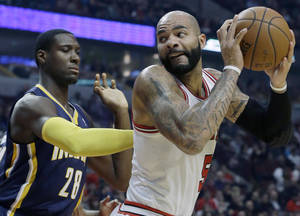 Photo - Chicago Bulls forward Carlos Boozer (5) looks to the basket as Indiana Pacers center Ian Mahinmi (28) guards during the first half of an NBA preseason basketball game in Chicago on Friday, Oct. 18, 2013. (AP Photo/Nam Y. Huh)