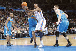 photo - Oklahoma City Thunder small forward Kevin Durant (35) looses the ball under the defense of New Orleans Hornets small forward Trevor Ariza (1) during the NBA basketball game between the Oklahoma City Thunder and the New Orleans Hornets at the Chesapeake Energy Arena on Wednesday, Jan. 25, 2012, in Oklahoma City, Okla. Photo by Chris Landsberger, The Oklahoman