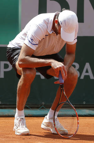 Photo - Croatia's Ivo Karlovic looks down as he plays South Africa's Kevin Anderson during their third round match of  the French Open tennis tournament at the Roland Garros stadium, in Paris, France, Saturday, May 31, 2014. (AP Photo/Michel Euler)
