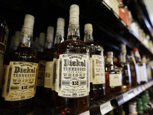 Photo - Bottles of George Dickel Tennessee whiskey are displayed in a liquor store Tuesday, June 10, 2014, in Nashville, Tenn. Alcohol regulators ended their investigation into whether George Dickel, a subsidiary of liquor giant Diageo, violated state laws by storing whiskey in neighboring Kentucky. (AP Photo/Mark Humphrey)