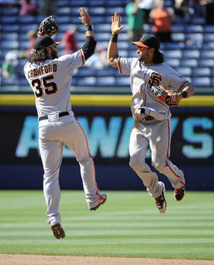 Photo - San Francisco Giants' Brandon Crawford (35) and Angel Pagan celebrate their 4-1 win over the Atlanta Braves after the ninth inning of a baseball game Sunday, May 4, 2014, in Atlanta. (AP Photo/David Tulis)