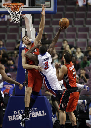 Photo -   Detroit Pistons guard Rodney Stuckey (3) drives on Toronto Raptors center Jonas Valanciunas, left, of Lithuania, and Jose Calderon (8), of Spain, in the first half of a preseason NBA basketball game in Auburn Hills, Mich., Wednesday, Oct. 10, 2012. (AP Photo/Paul Sancya)