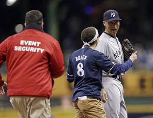 Photo - A fan runs out on the field to New York Yankees' Derek Jeter, right, in the sixth inning of a baseball game against the Milwaukee Brewers, Friday, May 9, 2014, in Milwaukee. (AP Photo/Jeffrey Phelps)