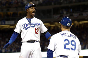 Photo - Los Angeles Dodgers' Hanley Ramirez (13) reacts as third base coach Tim Wallach (29) watches, after Ramirez hit an RBI triple against the Atlanta Braves during the fourth inning in Game 3 of the National League division baseball series Sunday, Oct. 6, 2013, in Los Angeles. (AP Photo/Danny Moloshok)
