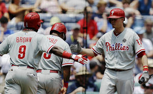 Photo - Philadelphia Phillies' Reid Brignac, right, high-fives teammates Marlon Byrd, center, and Domonic Brown after they scored off a single by John Mayberry Jr. in the second inning of a baseball game against the Atlanta Braves, Wednesday, June 18, 2014, in Atlanta. (AP Photo/David Goldman)
