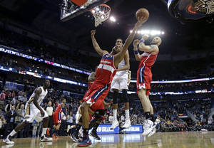 Photo - Washington Wizards small forward Trevor Ariza (1) battles for a rebound in front of center Marcin Gortat, right, and New Orleans Pelicans center Alexis Ajinca, behind, in the first half of an NBA basketball game in New Orleans, Wednesday, Jan. 8, 2014. (AP Photo/Gerald Herbert)