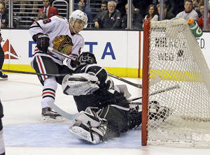 Photo - Chicago Blackhawks right winger Patrick Kane (88) tips the puck into the goal past Los Angeles Kings goalie Jonathan Quick (32) in the third period of an NHL hockey game in Los Angeles, Monday, Feb. 3, 2014. The Blackhawks won 5-3. (AP Photo/Reed Saxon)