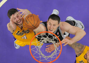 Photo - San Antonio Spurs forward Aron Baynes, right, of Australia, reaches for a rebound along with Los Angeles Lakers forward Ryan Kelly during the first half of their NBA basketball game, Wednesday, March 19, 2014, in Los Angeles. (AP Photo/Mark J. Terrill)