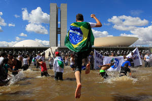 Photo - Demonstrators from the national student union gather inside the reflection pool outside Congress to demand 10 percent of the country's GDP be spent on public education in Brasilia, Brazil, Thursday, June 27, 2013.  The wave of protests that hit Brazil on June 17 began as opposition to transportation fare hikes, then expanded to a list of causes including anger at high taxes, poor services and high World Cup spending, before coalescing around the issue of rampant government corruption. (AP Photo/Eraldo Peres)