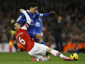 Photo - Arsenal's Laurent Koscielny, left, tackles Everton's Steven Pienaar during the English Premier League soccer match between Arsenal and Everton at the Emirates Stadium in London, Sunday, Dec. 8, 2013. (AP Photo/Kirsty Wigglesworth)