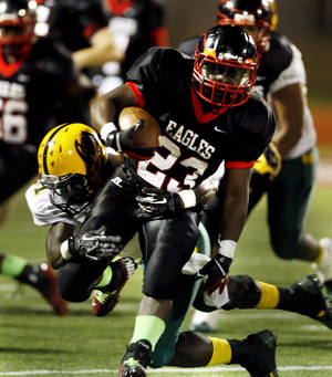 Photo - Del City's Anthony Mason carries as MacArthur's Devontre Young tries to tackle him during a high school football game between the Lawton MacArthur Highlanders and the Del City Eagles on Friday, Sept. 27, 2013 in Del City, Okla. Photo by Steve Sisney, The Oklahoman