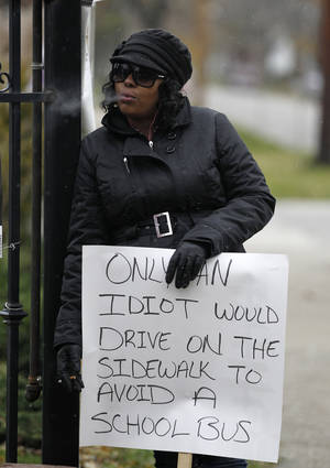 Photo -   Shena Hardin smokes a cigarette as she holds up a sign to serve a highly public sentence Tuesday, Nov. 13, 2012, in Cleveland, for driving on a sidewalk to avoid a Cleveland school bus that was unloading children. A Cleveland Municipal Court judge ordered 32-year-old Hardin to serve the highly public sentence for one hour Tuesday and Wednesday. (AP Photo/Tony Dejak)