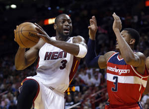 Photo - Miami Heat's Dwyane Wade (3) prepares to shoot against Washington Wizards' Bradley Beal (3) during the first half of an NBA basketball game in Miami, Sunday, Jan. 6,  2013. (AP Photo/Alan Diaz)