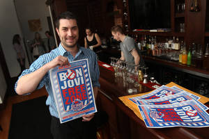 Photo - In this May 21, 2014 photo, Anthony Lynch displays a Bon Jovi Free Zone poster at Savoy in Buffalo, N.Y.  Livin' on a prayer isn't part of the plan for Buffalo Bills fans. Not content to sit back and hope for the best as their beloved NFL team is sold, they are doing everything they can to influence the next owner to keep the franchise in Buffalo. That includes trying to raise millions of dollars as an incentive to keep the team where it is, circulating petitions and even organizing a ban on Bon Jovi music because the band's frontman is rumored to want to buy the team and move it to Canada. (AP Photo/The Buffalo News, Sharon Cantillon)
