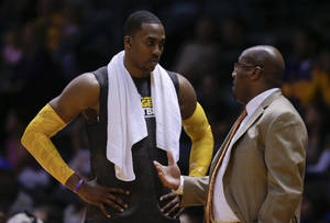 Photo -   Los Angeles Lakers center Dwight Howard, left, talks with head coach Mike Brown during the second half of a preseason NBA basketball game against the Sacramento Kings on Thursday, Oct. 25, 2012, in San Diego. (AP Photo/Gregory Bull)