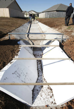 Photo - A trough will be used to measure and compare water runoff against a comparable nearby street using a natural system for runoff water filtration in Norman's Trail Woods addition.PHOTO BY PAUL HELLSTERN, THE OKLAHOMAN