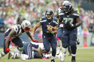 Photo -   Seattle Seahawks quarterback Russell Wilson (3) carries the ball as teammate James Carpenter (77) blocks and New England Patriots linebacker Brandon Spikes, left, moves in for the tackle in the first half of an NFL football game, Sunday, Oct. 14, 2012, in Seattle. (AP Photo/Elaine Thompson)