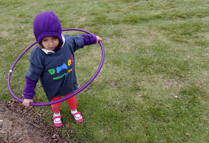 Photo - Catalina Mino, 3, plays with a hula hoop during the YMCA 5210 event at Myriad Gardens. Photos by Sarah Phipps, The Oklahoman