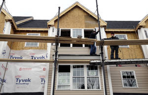 photo - In this Dec. 20, 2012 photo, a builder works in North Andover, Mass., where condominium units are under construction. Spending on U.S. construction projects rose in December, ending a year in which construction activity increased for the first time in six years. (AP Photo/Elise Amendola)