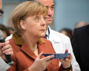photo - German Chancellor Angela Merkel looks up after smelling at coffee beans during the opening tour of the 'International Green Week' in Berlin, Germany, Friday, Jan. 18, 2013. International Green Week opens to the public from Jan. 18 until Jan. 27, 2013. (AP Photo/dpa, Michael Kappeler)