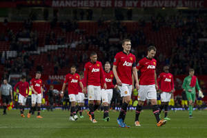 Photo - Manchester United players walk from the pitch after their 2-1 loss to Swansea City in their English FA Cup third round soccer match at Old Trafford Stadium, Manchester, England, Sunday Jan. 5, 2014. (AP Photo/Jon Super)