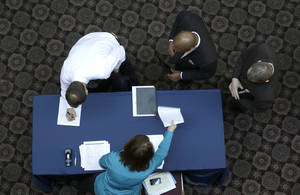 Photo - In this Wednesday, Jan. 22, 2014, file photo, job seekers sign in before meeting prospective employers during a career fair at a hotel in Dallas. Labor Department releases weekly jobless claims on Thursday, Jan. 30, 2014. (AP Photo/LM Otero)