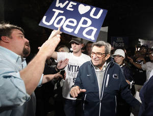 "photo - Scott Paterno, left, looks on as students greet his father Penn State football coach Joe Paterno as he arrives at his home, Tuesday, Nov. 8, 2011, in State College, Pa. Paterno's support among the Penn State board of trustees was described as ""eroding"" Tuesday, threatening to end the 84-year-old coach's career amid a child sex-abuse scandal involving a former assistant and one-time heir apparent. (AP Photo/Matt Rourke) ORG XMIT: PAMR127"