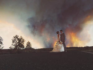 Photo - In this Saturday, June 7, 2014 photo provided by Josh Newton, newlyweds Michael Wolber and April Hartley pose for a picture near Bend, Ore., as a wildfire burns in the background. Because of the approaching fire, the minister conducted an abbreviated ceremony and the wedding party was evacuated to a downtown Bend park for the reception. (AP Photo/Josh Newton)