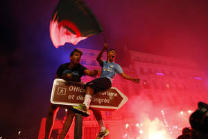 Photo - Algerian soccer fans celebrate after their team qualified for the World Cup, in Marseille, southern France, Thursday, June 26, 2014. Algeria drew with Russia 1-1, and advanced to the round of 16 for the first time in their World Cup history. (AP Photo/Claude Paris)