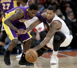 Photo - Los Angeles Lakers' Manny Harris, left, and New York Knicks' Jeremy Tyler fight for the ball during the second half of an NBA basketball game at Madison Square Garden Sunday, Jan. 26, 2014, in New York. The Knicks won 110-103. (AP Photo/Seth Wenig)