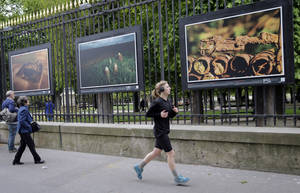 "Photo - A woman runs next to ""  ""A rusting rifle"" a  picture by British photographer Michael St Maur Sheil at the Paris Luxembourg gardens, Tuesday, April 8, 2014 as part of an exhibition "" Fields of Battle - Lands of Peace 14-18 "". Captured over a period of seven years, Michael's photography combines a passion for history and landscape and presents a unique reflection on the transformation of the battlefields of the Great War into the landscape of modern Europe. (AP Photo/Christophe Ena)"