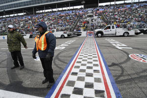 Photo - Track security guards Patrick Reyes, left, and Richard Gyure stand by the start-finish line as jet dryers blow dry the strait away before a rain delayed start of the NASCAR Sprint Cup Series auto race at Texas Motor Speedway in Fort Worth, Texas, Sunday, April 6, 2014. (AP Photo/Ralph Lauer)