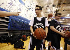 Photo - Van Hoosen's Owen Groesser warms up after halftime of a middle school basketball game against Reuther, Thursday, Jan. 24, 2013, at Rochester High School in Rochester, Mich. Groesser, an eight-grader with Dwon Syndrome, made ESPN'S SportsCenter Top 10 Plays after hitting two 3-pointers in the first game he got to play this season on Wednesday. (AP Photo/Detroit Free Press, Andre J. Jackson)  DETROIT NEWS OUT;  NO SALES; MAGS OUT; MANDATORY CREDIT
