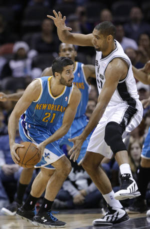 Photo - New Orleans Hornets' Greivis Vasquez, left, looks to move the ball against San Antonio Spurs' Tim Duncan during the first quarter of an NBA basketball game, Friday, Dec. 21, 2012, in San Antonio. (AP Photo/Eric Gay)