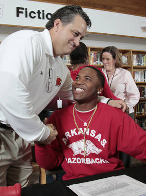 Photo - Head coach Greg Norman hugs Norman High school player Donovan Roberts after he signed a letter of intent to play for Arkansas on Wednesday, Feb. 1, 2012, in Norman, Okla.   Photo by Steve Sisney, The Oklahoman