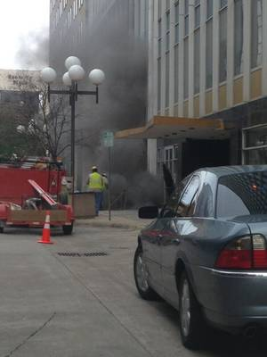 Photo - Utility crews are seen hovering over an underground utility tunnel following a transformer explosion in front of the First National Center at Park and Broadway about 6 p.m. Friday. <strong>Courtesy Marek Cornett</strong>