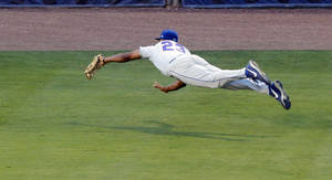Photo - Florida's Buddy Reed makes a diving catch against Mississippi State during the third inning at the Southeastern Conference NCAA college baseball tournament on Friday, May 23, 2014, in Hoover, Ala. (AP Photo/Butch Dill)