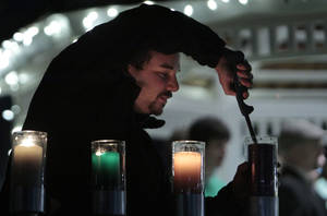 photo - OU senior Matthew Lorch lights menorah candles at the University of Oklahoma's holiday lights celebration in Norman.