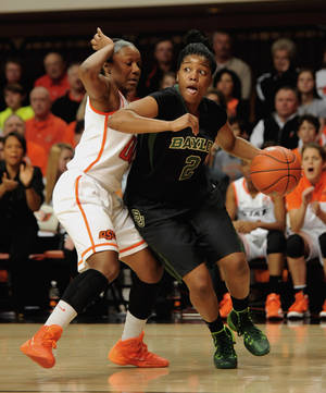 Photo - Baylor guard Niya Johnson, right, drives past Oklahoma State guard Roshunda Johnson, during the first half of an NCAA college basketball game in Stillwater, Okla., Sunday, Jan. 26, 2014. (AP Photo/Brody Schmidt)