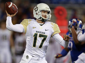 Photo - Baylor Bears quarterback Seth Russell throws in the third quarter of an NCAA college football game against the Kansas Jayhawks, Saturday, Oct. 26, 2013, in Lawrence, Kan. Baylor won 59-14. (AP Photo/Ed Zurga)