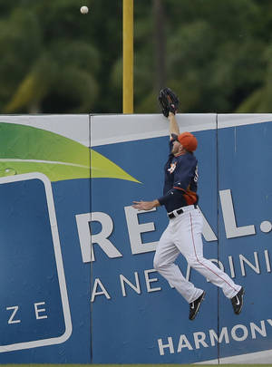Photo - Houston Astros left fielder Robbie Grossman jumps but can not reach the two-run home run by New York Mets' Anthony Recker during the fifth inning of a spring exhibition baseball game in Kissimmee, Fla., Wednesday, March 26, 2014. (AP Photo/Carlos Osorio)